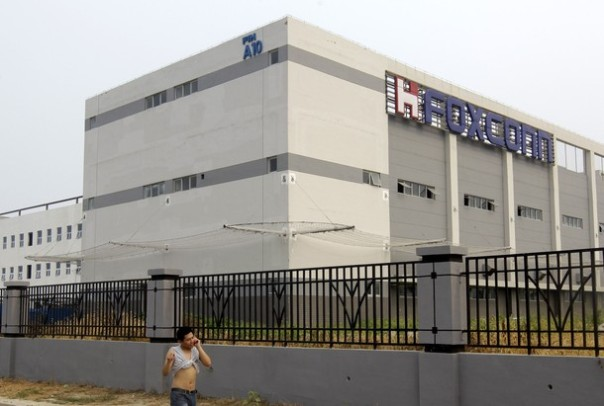 A man walks outside one of the Foxconn factory buildings with the nets, installed to prevent workers from jumping to their deaths, in Langfang, Hebei Province August 3, 2010. Taiwan's Hon Hai Precision Industry Co Ltd , also known as Foxconn Technology Group, opened a new $100 million production factory in the central Chinese province of Henan, as the group began to move production inland in a bid to cap rising labour costs, according to a state media report. REUTERS/Jason Lee (CHINA - Tags: BUSINESS)