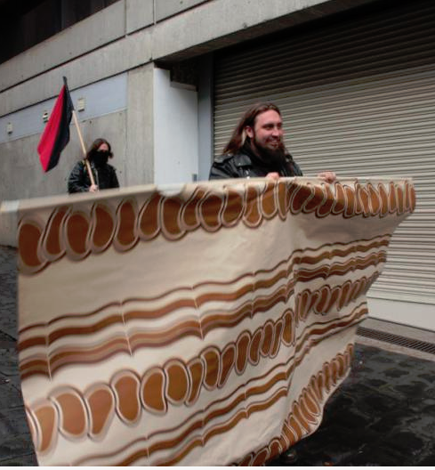 Police informant and Faketivist JASON MORGAN-GRAHAM organises fake protest with a suspicious character only known as Moo Kau. Here is MG (as he like to be known) carrying a curtain at a protest clearly mocking protesters.